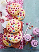 Giant cookies decorated with colourful chocolate beans and bottles of strawberry milkshake