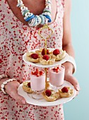 A woman holding a cake stand with panna cotta tartlets and strawberry mousse