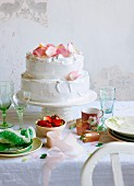 A pistachio and rose meringue cake with strawberry cream decorated with candid rose petals