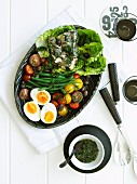 Salad nicoise on an oval platter with bowls of dressing