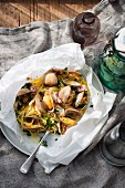 Linguine with clams and Pancetta en papillote on a table laid with maritime decorations