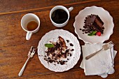 Piece of Chocolate Cake on a Plate; Dirty Plate with Cake Remains; Tea and Coffee