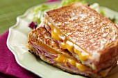 Grilled Ham and Cheese Sandwich; Halved and Stacked on a Plate