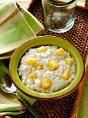 Small curd cottage cheese with pineapple chunks in green bowl on a woven tray