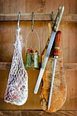 A net holding assorted types of salami, chillies, a knife and board