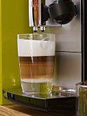 Latte macchiato beneath a coffee maker