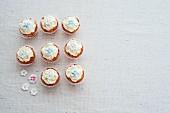Acht Cupcakes verziert mit Zuckerblüten (Aufsicht)