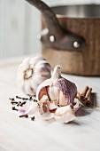 A still life featuring garlic, cloves and cinnamon sticks