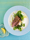 Marinated lamb fillet with mustard seeds on spinach leaves