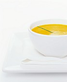 A white bowl of carrot soup with a single chive garnish
