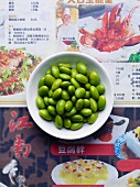 Edamame beans in a white dish on japanese newspaper