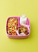 Pink lady apple and couscous salad, with apple flapjack, and bottle of milk, in a pink bento lunchbox