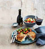 Breaded chicken escalope stuffed with provolone and olives, served with a tomato salad and red wine