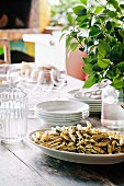 Stack of crockery and a dish of pasta on a table in a garden