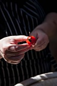 A tomato being skewered