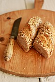 Halved wholegrain baguette with a knife on a wooden board