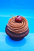 A cupcake topped with chocolate buttercream and a cherry