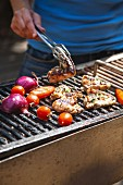 Chicken wings and vegetables on the barbecue