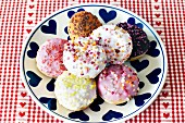 Colourfully decorated doughnuts on a plate with a heart pattern
