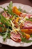 A salad of boiled ham, rocket, walnuts, yellow plums and cheese