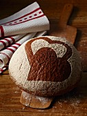 A bread roll decorated with a heart design