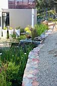 Terrassengarten teilweise gekiest vor zeitgenössischem Wohnhaus