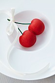 Marzipan cherries with a bow on a plate
