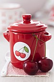 Cherry jam in a red pot with a cherry sticker