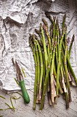 Green asparagus and a peeler on newspaper