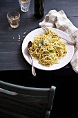 Spaghetti with pesto on a rustic wooden table