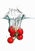 Tomatoes falling into water