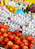 A market stall with tomatoes, garlic, lemons and onions