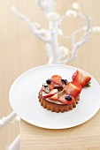 Individual white chocolate torte topped with strawberries and blueberries