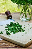Chopped parsley with a mezzaluna on a wooden board