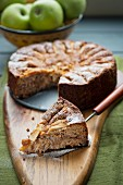 Apple cake with a slice removed and fresh apples