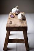 Fresh garlic bulbs on a wooden stool