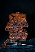 Stack of chocolate brownies with a whisk dipped in melted chocolate