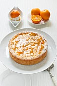 orange cake on a cake stand with fresh oranges
