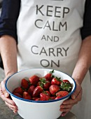 Fresh strawberries and an apron with a logo