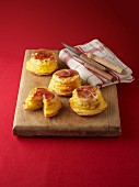 Small upside-down potato muffins with bacon on a wooden board