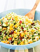 Bowl of Quinoa Salad with a Wooden Spoon
