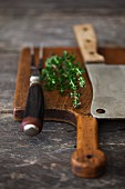 Thyme with a Carving Fork and Knife on a Cutting Board