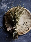 Dried mugwort, tied in a bunch with a label, on a wooden plate