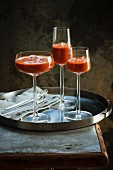 Gazpacho with ice served in stemmed glasses on a tray