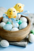 Easter chick cape pops and chocolate eggs in a wooden bowl