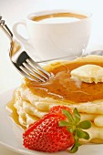 A Fork Piercing Pancakes with Butter and Maple Syrup; Cup of Coffee