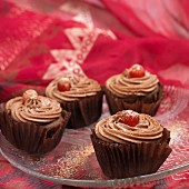 Chocolate cupcakes with glacé cherries on a glass plate
