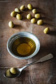 Green olives and olive oil on a wooden table