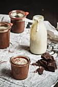 Three jars of chocolate dessert and a glass of vanilla sauce on newspaper