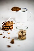 A stack of biscuits, a mug with a biscuit on the edge and a glass of walnuts